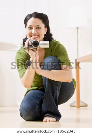 Happy woman kneeling and making video with video camera - stock photo