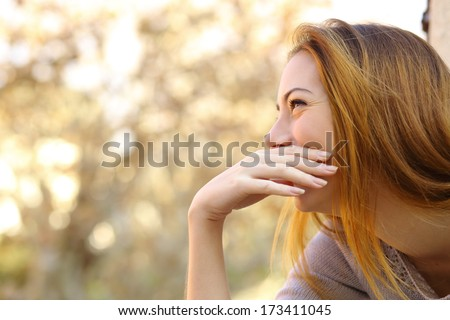 Happy woman laughing covering her mouth with a hand with a warmth background - stock photo