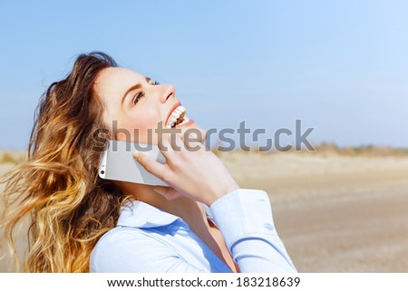 Happy woman laughing on the mobile phone on the seaside - stock photo