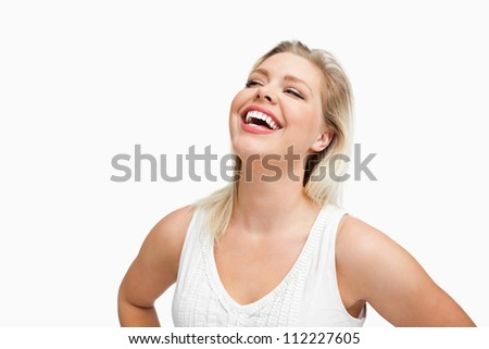 Happy woman laughing with her hands on her hips against a white background