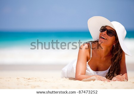 Happy woman laying at the beach wearing a hat on a summer day - stock photo