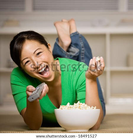 Happy woman laying on floor with bowl of popcorn, remote control and watching television - stock photo