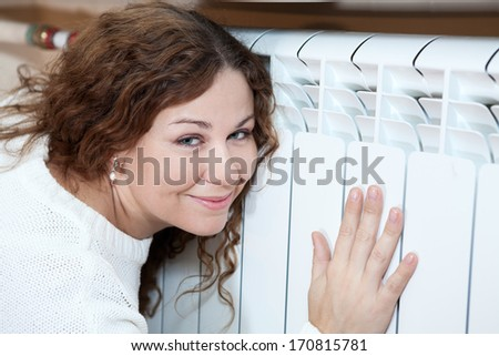Happy woman leaning his to central heating radiator - stock photo