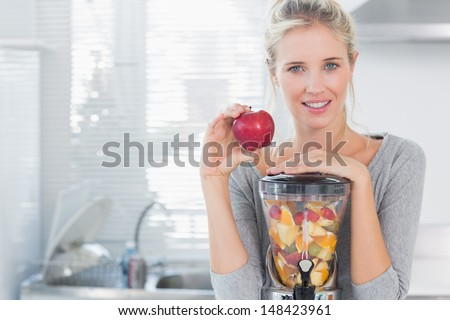 Happy woman leaning on her juicer full of fruit and holding red apple looking at camera at home in kitchen - stock photo