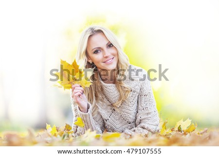 Happy woman lies on dry leaves in autumn park at sunny day