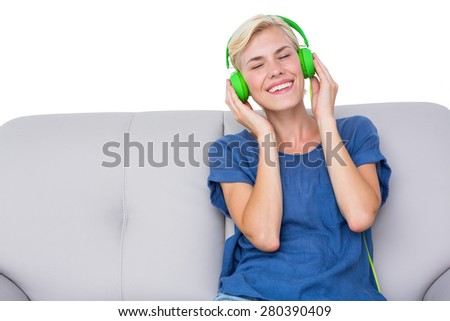 Happy woman listening music on the couch on white background - stock photo