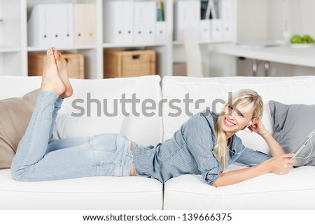 Happy woman listening to music and lying on a white couch with tablet - stock photo