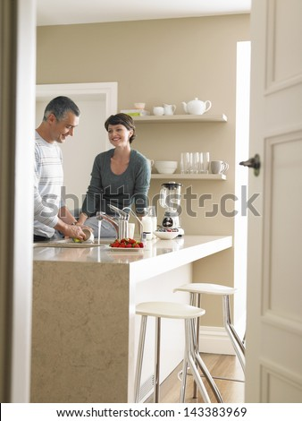 Happy woman looking at man washing utensils at kitchen counter