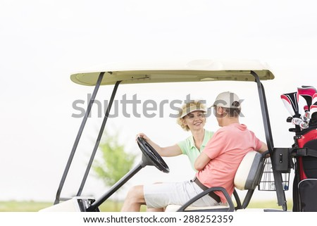 Happy woman looking at man while sitting in golf cart - stock photo