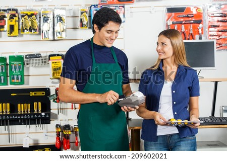 Happy woman looking at worker swiping credit card for screwdriver set in hardware store