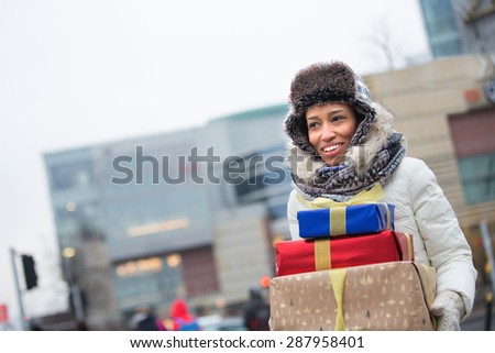 Happy woman looking away while carrying stacked gifts during winter - stock photo