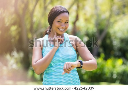 Happy woman looking her watch at park - stock photo