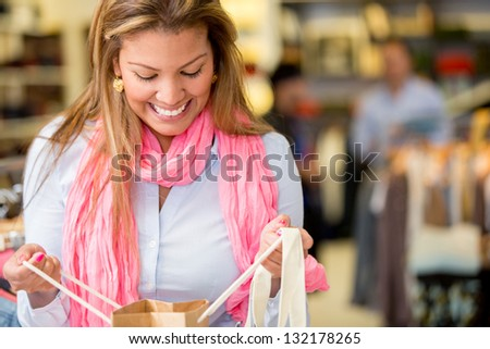 Happy woman looking into a shopping bag - stock photo