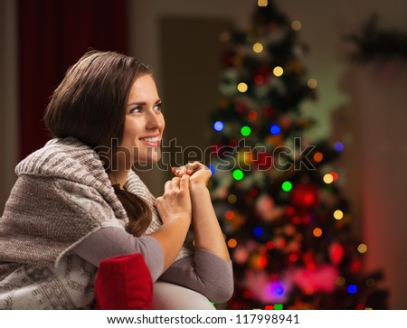 Happy woman looking on copy space and Christmas tree in background - stock photo