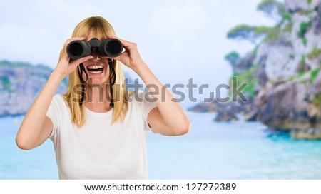 happy woman looking through binoculars at a beach - stock photo