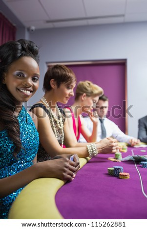 Happy woman looking up from poker game in casino - stock photo
