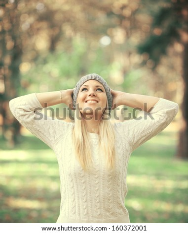 Happy woman looking up in the sky in Autumn forest - stock photo