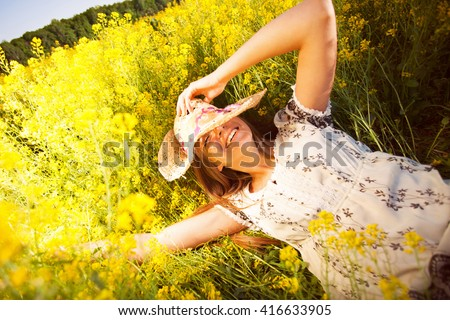 Happy woman lying among yellow wildflowers in summer