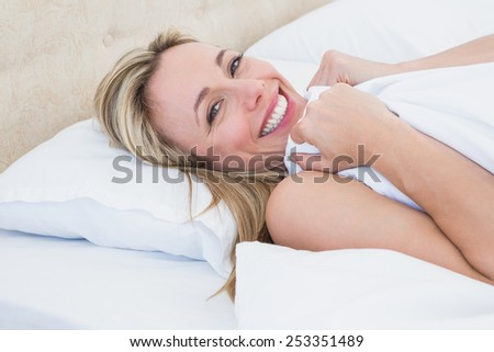Happy woman lying in bed under duvet at home in the bedroom - stock photo