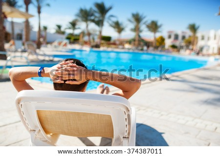 happy woman lying on a lounger by the pool at the hotel.