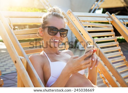 Happy woman lying on a sun lounger by the pool with a mobile phone - stock photo