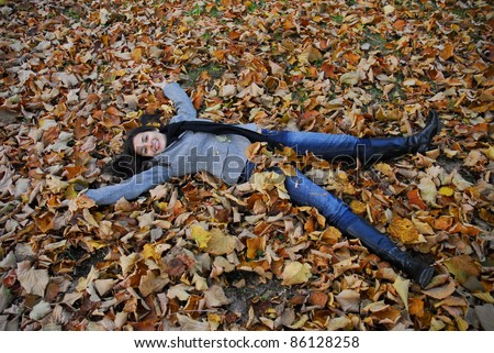 Happy woman lying on autumn leaves.Woman fall. - stock photo
