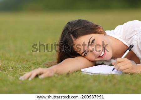 Happy woman lying on the grass and writing in a notebook with unfocused green background