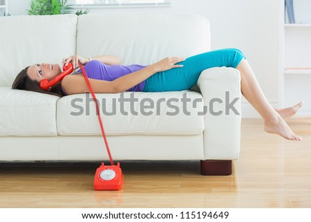 Happy woman lying on the sofa and phoning in the living room - stock photo