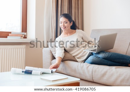 Happy woman lying on the sofa with laptop computer and stretching hand to take magazine