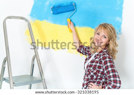 Happy woman makes repairs at home - painting wall at room. Portrait of smiling woman painting big Ukrainian flag on wall at home. - stock photo
