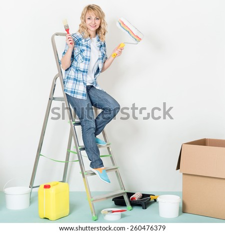 Happy woman makes repairs at home. Smiling beautiful young woman with roller and brush on a ladder. - stock photo