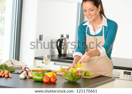 Happy woman making salad kitchen vegetables cooking food