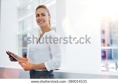 Happy woman manager holding touch pad and thinking about something good while standing in modern office interior,young smart female secretary smiling for someone during work on portable digital tablet - stock photo