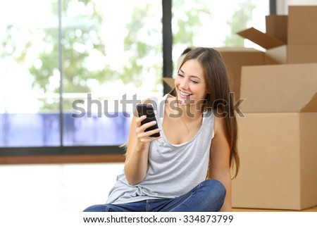 Happy woman moving home texting in a smart phone siting on the floor - stock photo