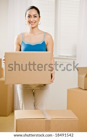 Happy woman moving into new home and carrying cardboard box - stock photo