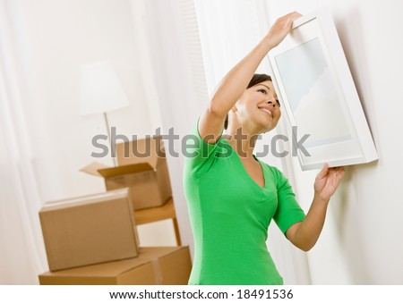 Happy woman moving into new home hanging picture on wall - stock photo