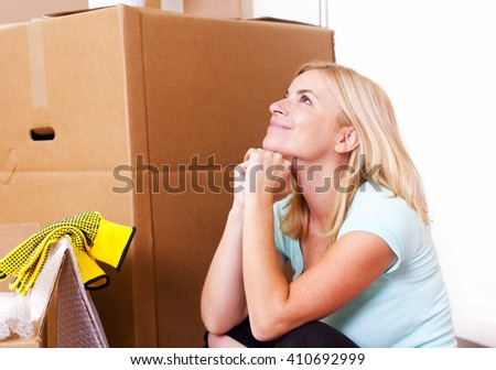 Happy woman moving, surrounded by large carton boxes and packing material. - stock photo