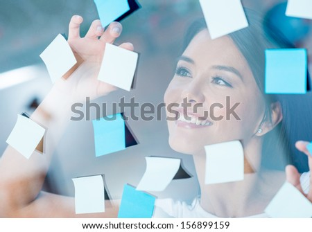 Happy woman multitasking with post-its all over the place - stock photo