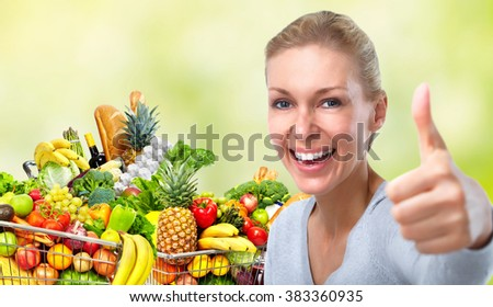Happy woman near shopping cart with food.