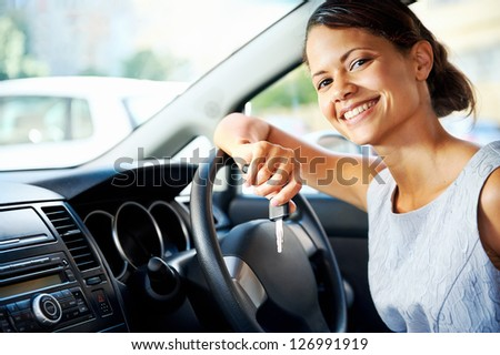 Happy woman new car owner smiling and showing keys in driver seat - stock photo