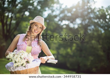 Happy woman on a bicycle outdoors - stock photo