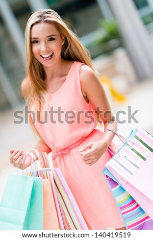 Happy woman on a shopping spree holding bags