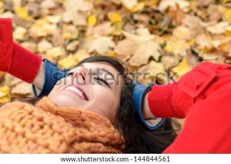 Happy woman on autumn season relax. Brunette girl lying down and smiling on fall golden leaves in park. Tranquility and peace concept.