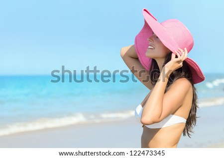 Happy woman on beach summer holidays. Caucasian young model with pink straw hat looking the sea. Copyspace. - stock photo