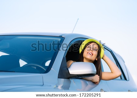 Happy woman on car summer roadtrip enjoying freedom. Beautiful brunette smiling and looking up. - stock photo