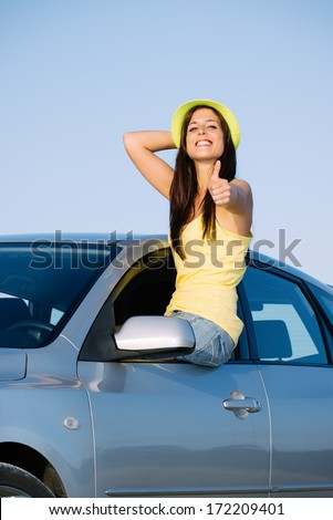 Happy woman on car travel doing approving thumbs up gesture. Brunette girl enjoying summer roadtrip. - stock photo