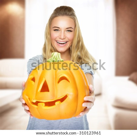 Happy woman on Halloween party at home, holding in hands pumpkin with carved face, having fun on traditional autumn holiday, decorating home  - stock photo