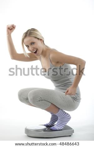 Happy woman on scale - stock photo