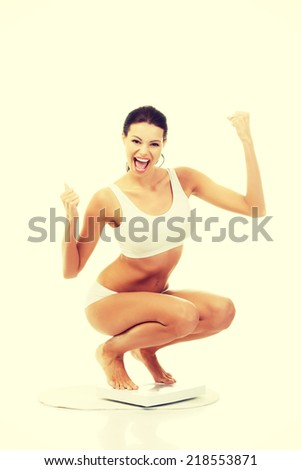 Happy woman on scales. Weight-loss concept. - stock photo