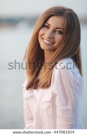 Happy woman on the beach Portrait of the beautiful girl close-up, Close up sunny summer portrait of beautiful woman with fluffy brunette long hairs, smiling, having fun near blue ocean,